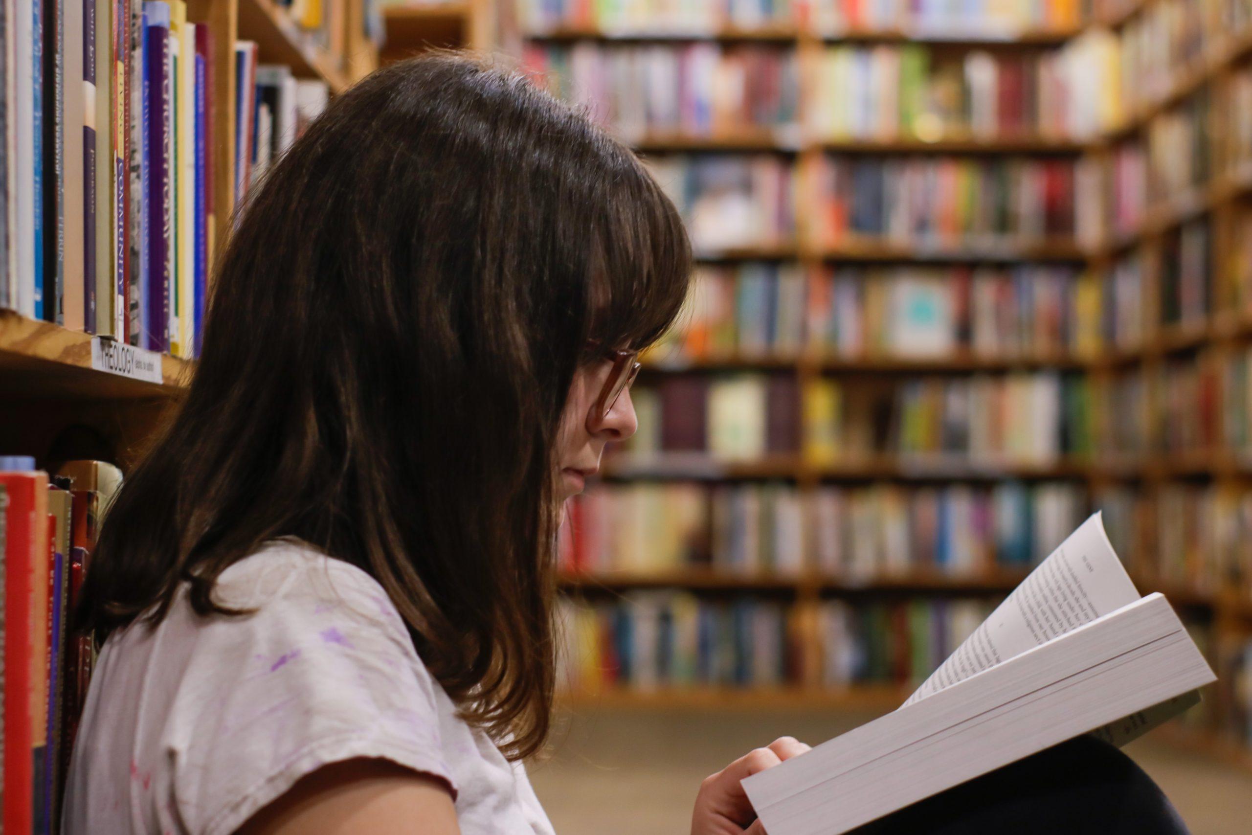 Jonge vrouw leest boek in bibliotheek